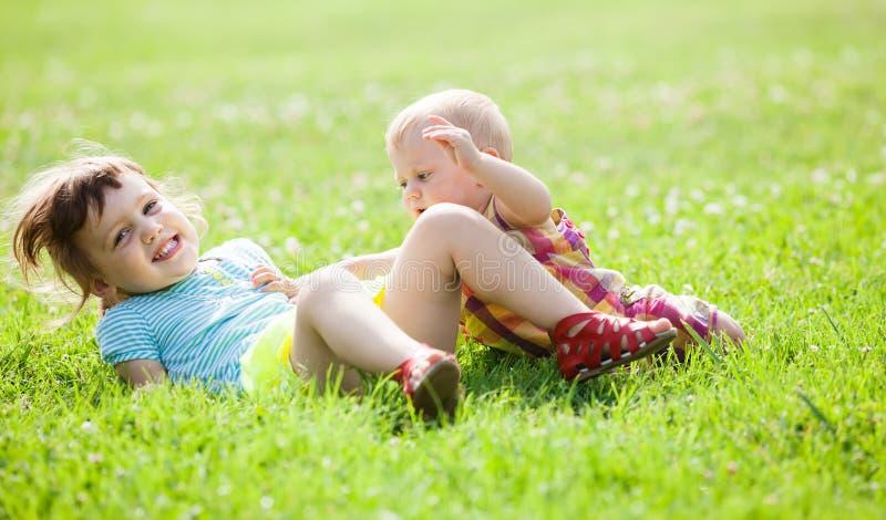 Lyckliga barn som spelar i gräs royaltyfri fotografi