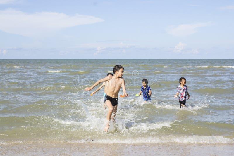 Lyckliga barn som spelar i havet arkivbilder