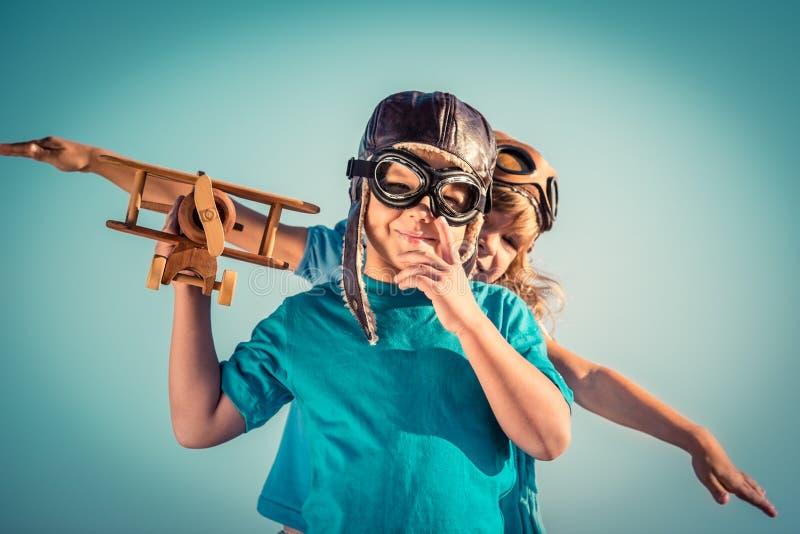Lyckliga barn som spelar med leksakflygplanet fotografering för bildbyråer