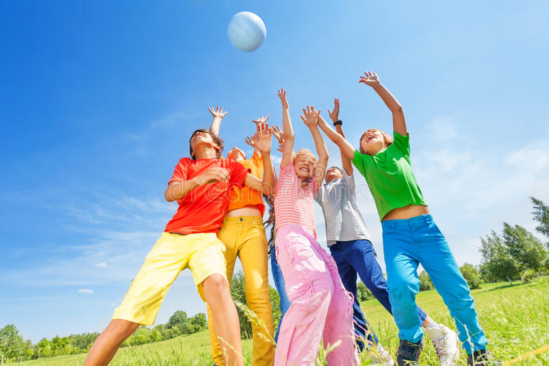 Lyckliga barn som spelar och fångar bollen fotografering för bildbyråer