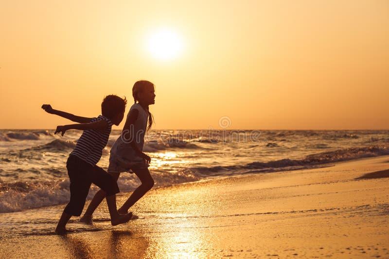 Lyckliga barn som spelar på stranden på solnedgångtiden royaltyfria foton