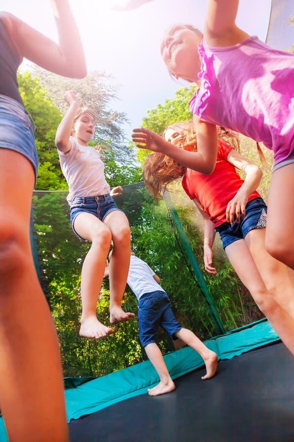 Lyckliga barn som tycker om att hoppa på trampolinen fotografering för bildbyråer