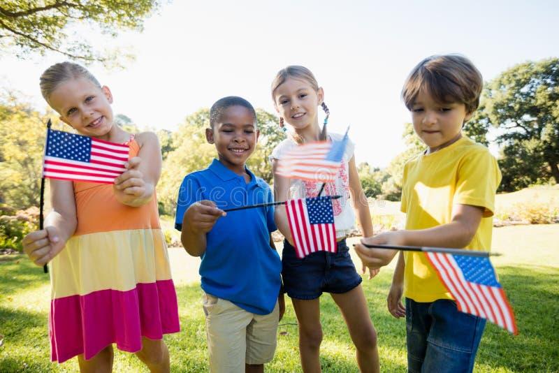 Lyckliga barn som visar USA-flaggan royaltyfri fotografi