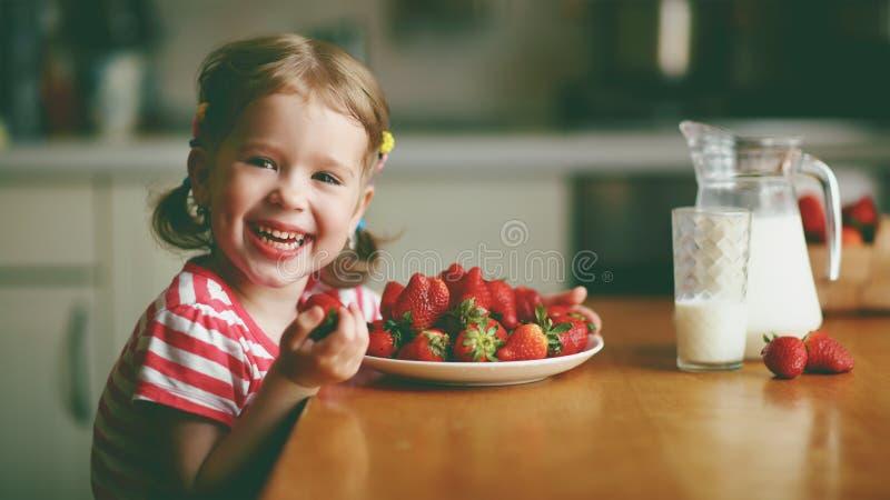 Lyckliga barnflickadrinkar mjölkar och äter jordgubbar i sommarhom arkivbild