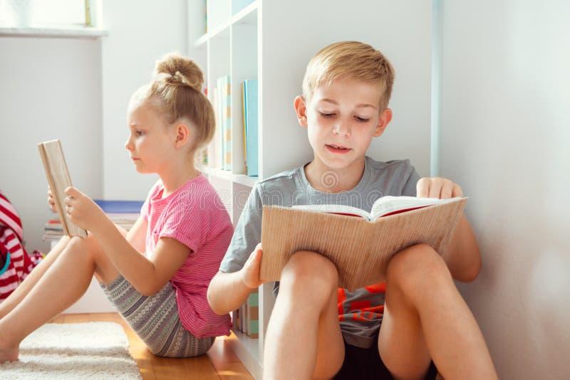 Lyckliga barnläseböcker på golvet på skolaarkivet fotografering för bildbyråer
