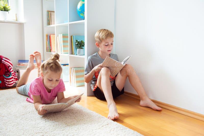 Lyckliga barnläseböcker på golvet på skolaarkivet royaltyfri bild