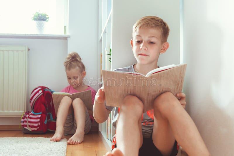 Lyckliga barnläseböcker på golvet på skolaarkivet royaltyfria foton