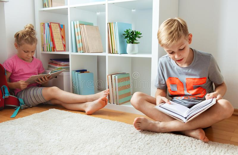 Lyckliga barnläseböcker på golvet på skolaarkivet arkivbilder