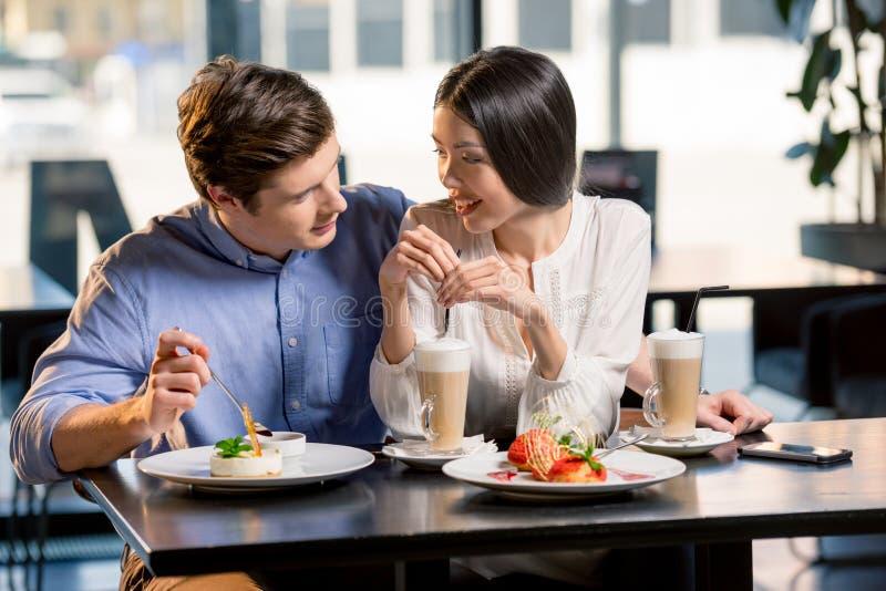 Lyckliga barnpar som är förälskade på det romantiska datumet i restaurang fotografering för bildbyråer