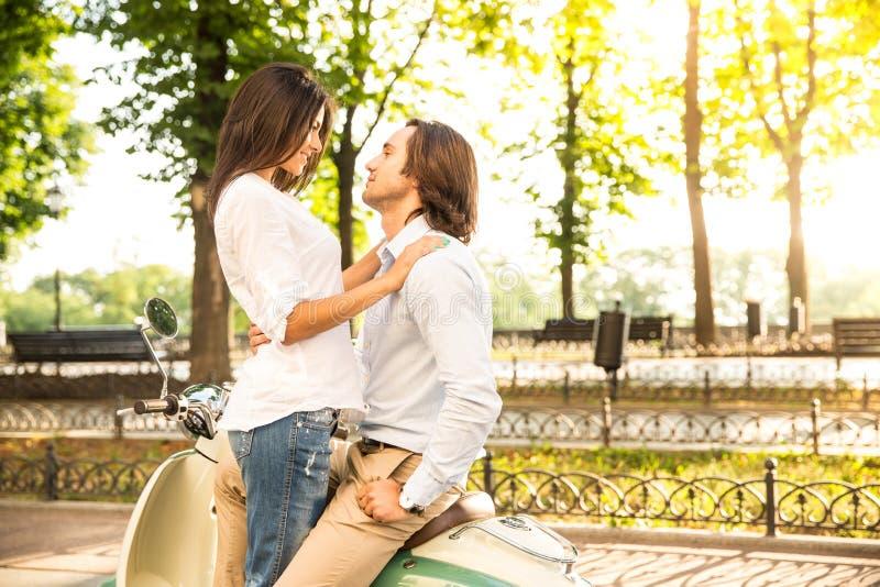 Lyckliga barnpar som flörtar på sparkcykeln royaltyfria foton