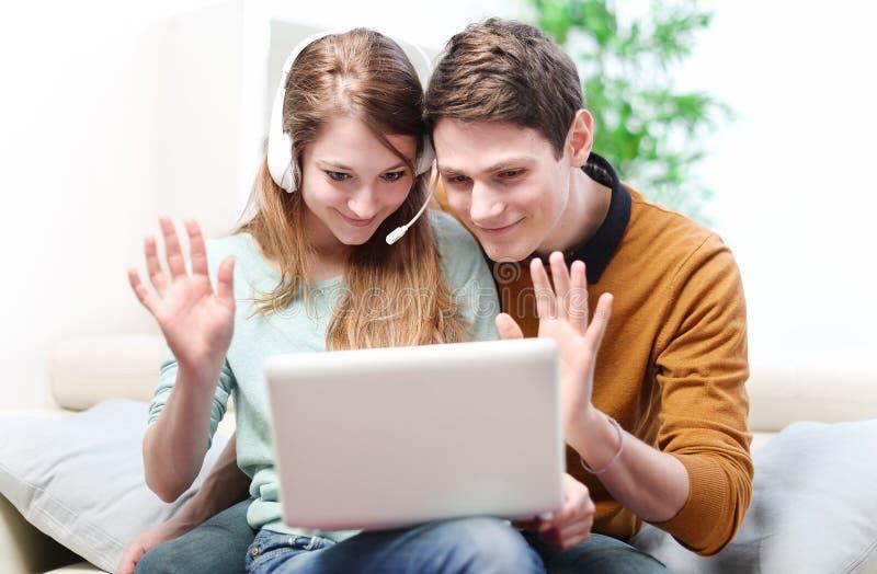 Lyckliga barnpar som talar till och med datoren med video pratstund royaltyfria bilder