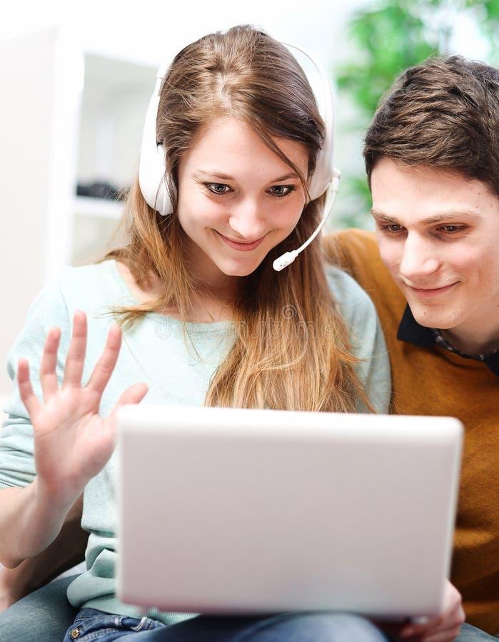 Lyckliga barnpar som talar till och med datoren med video pratstund royaltyfri foto