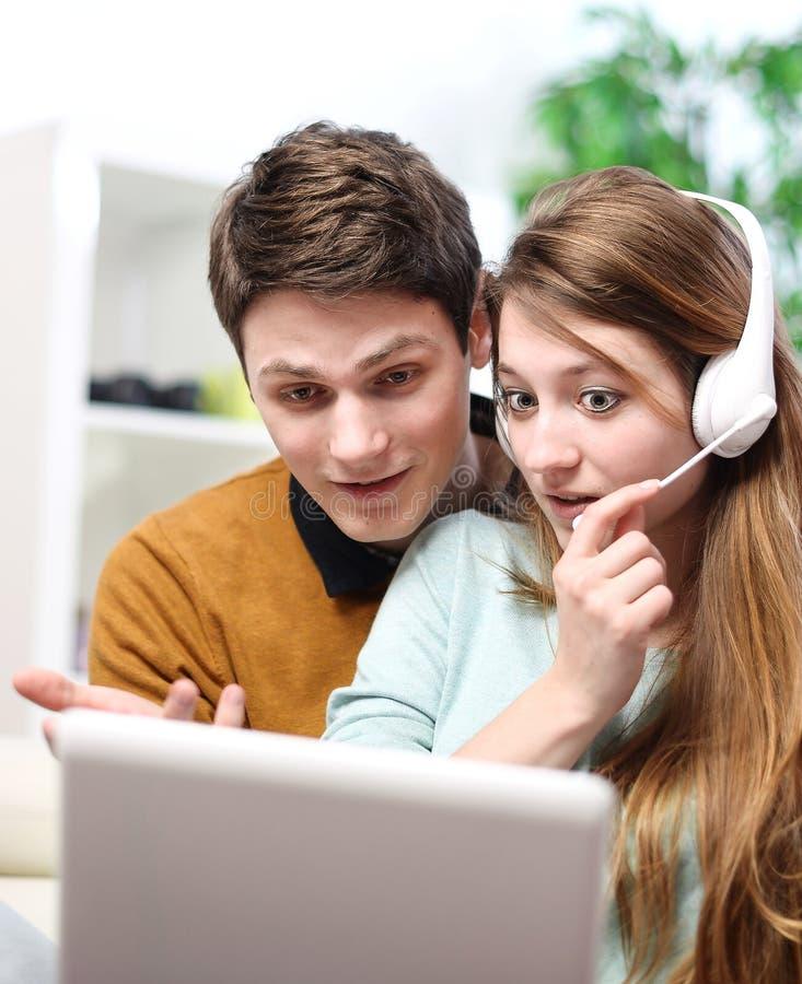 Lyckliga barnpar som talar till och med datoren med video pratstund royaltyfria foton