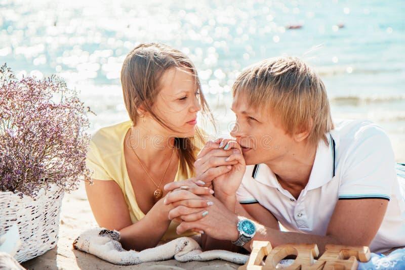 Lyckliga barnpar som tycker om picknicken på stranden och, har bra si arkivbild