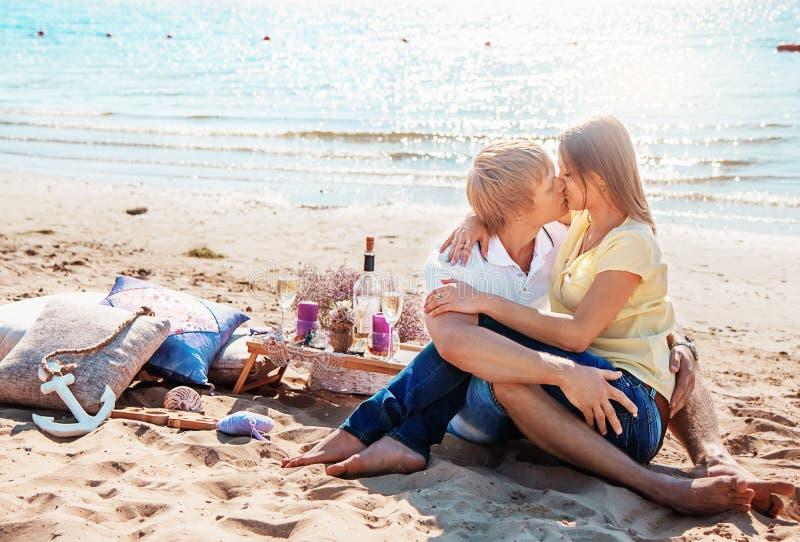Lyckliga barnpar som tycker om picknicken på stranden och, har bra si arkivfoto