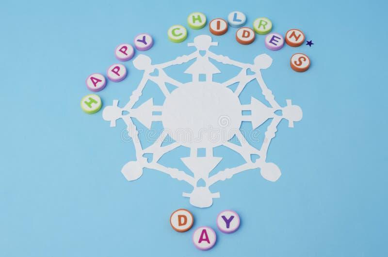 Lyckliga barns dag gjorde från färgrika bokstäver och pappers- dockakedja arkivfoton