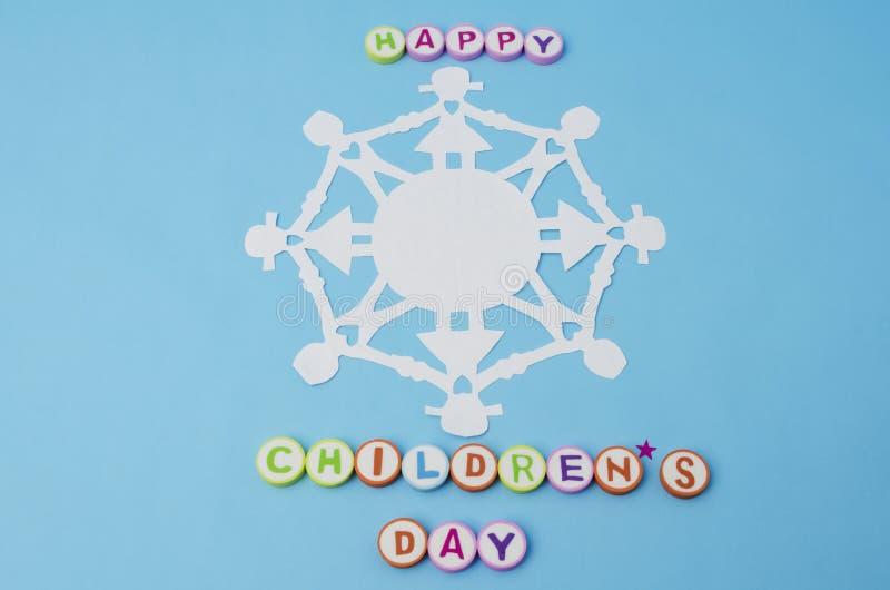 Lyckliga barns dag gjorde fr?n f?rgrika bokst?ver och pappers- dockakedja royaltyfria bilder