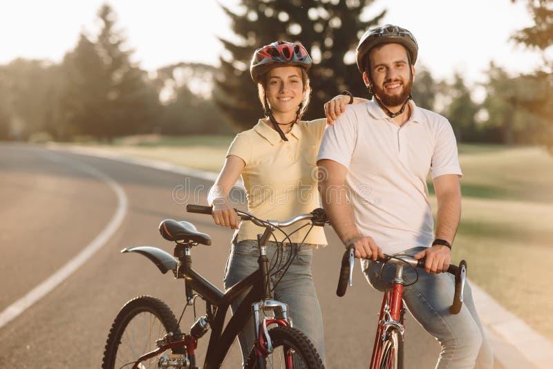 Lyckliga bekymmerslösa par med cyklar utomhus arkivfoto