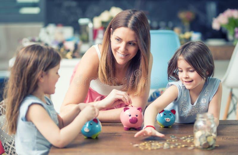 Lyckliga besparingar för investering för framtid för spargris för pengar för räddning för familjmammadotter fotografering för bildbyråer