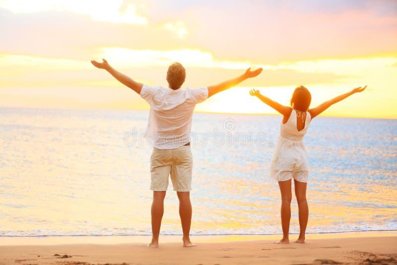 Lyckliga bifallpar som tycker om solnedgång på stranden arkivfoto