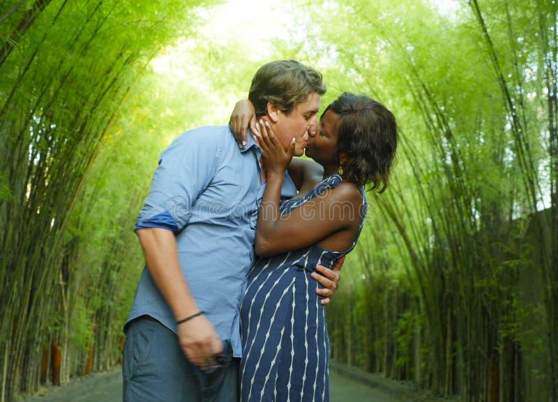 Lyckliga blandade etnicitetpar som utomhus kysser med den attraktiva svarta afrikansk amerikankvinnan och den stiliga Caucasian p royaltyfri bild