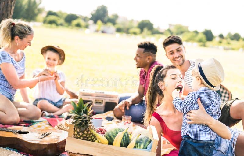 Lyckliga blandras- familjer som har gyckel med ungar på picknickgrillfestpartiet - mångkulturell lycka på glädje- och förälskelse royaltyfria foton