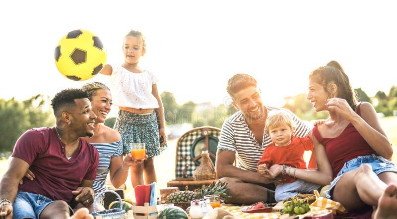 Lyckliga blandras- familjer som har gyckel samman med ungar på partiet för pic-nic-grillfest - mångkulturellt glädje- och förälsk royaltyfria foton