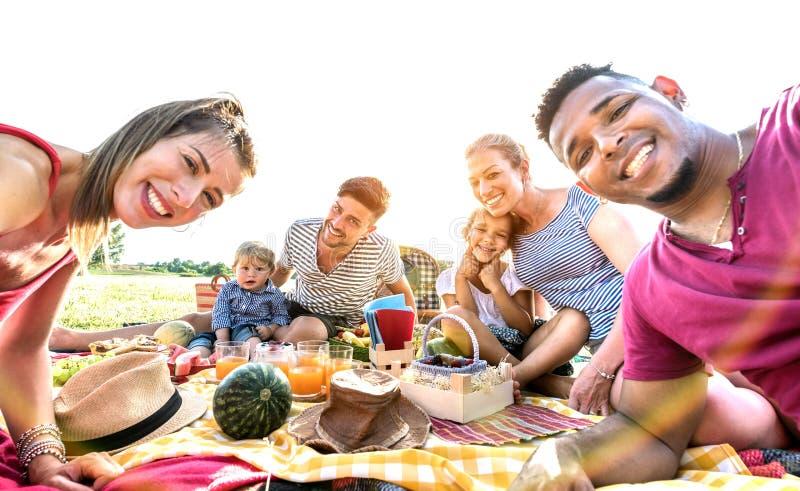 Lyckliga blandras- familjer som tar selfie på partiet för pic-nic-trädgård - mångkulturellt glädje- och förälskelsebegrepp med fo arkivbilder