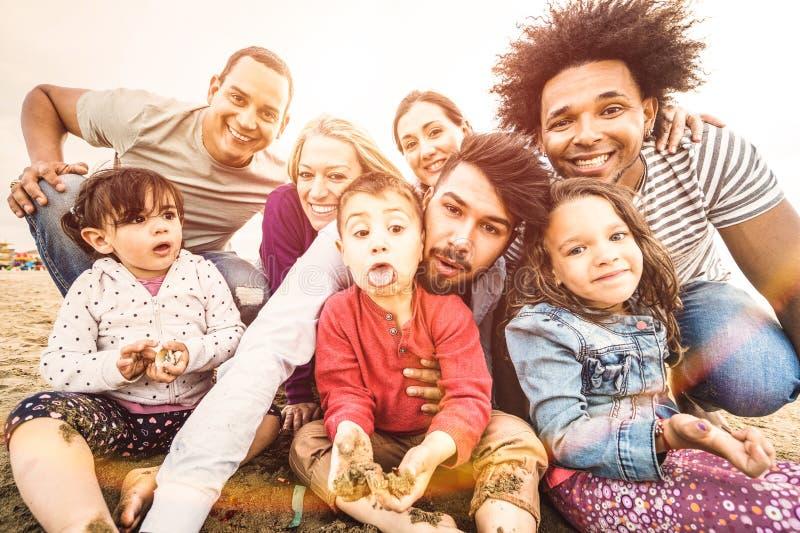 Lyckliga blandras- familjer som tar selfie på stranden som gör roliga framsidor royaltyfri foto