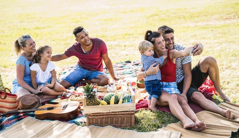 Lyckliga blandras- familjer som tar selfie p? partiet f?r pic-nic-tr?dg?rd - m?ngkulturellt gl?dje- och f?r?lskelsebegrepp med fo royaltyfri foto