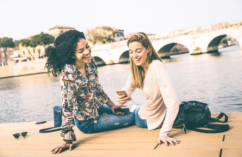 Lyckliga blandras- flickvänner som har gyckel med den smarta telefonen för mobil royaltyfri bild