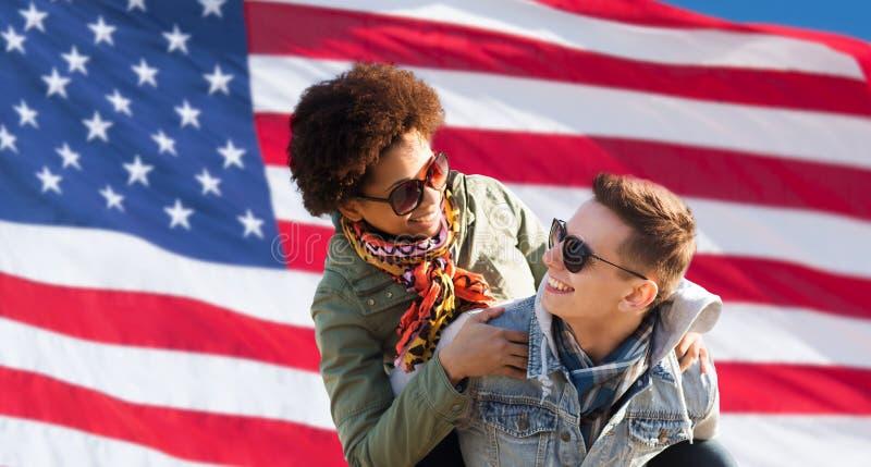 Lyckliga blandras- par över amerikanska flaggan arkivbild