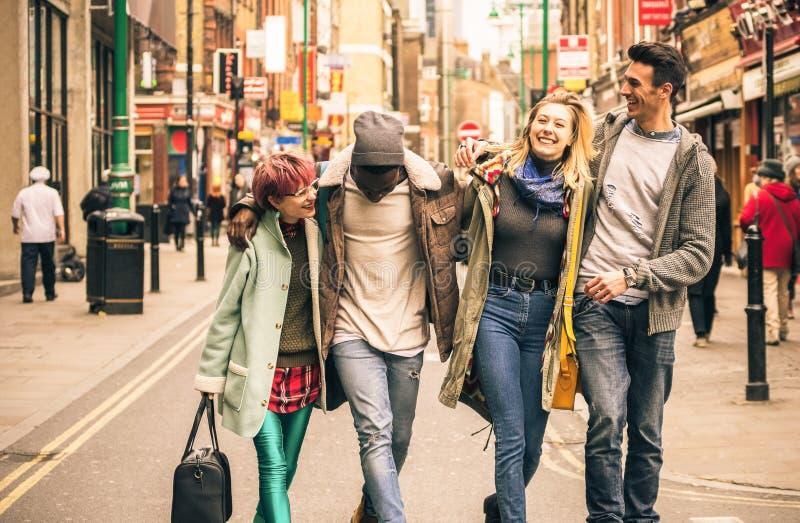 Lyckliga blandras- vänner som går på tegelstengränd på Shoreditch London arkivfoton