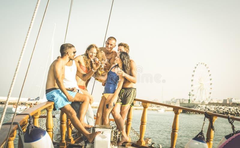 Lyckliga blandras- vänner som har gyckel på seglingpartifartyget arkivbilder