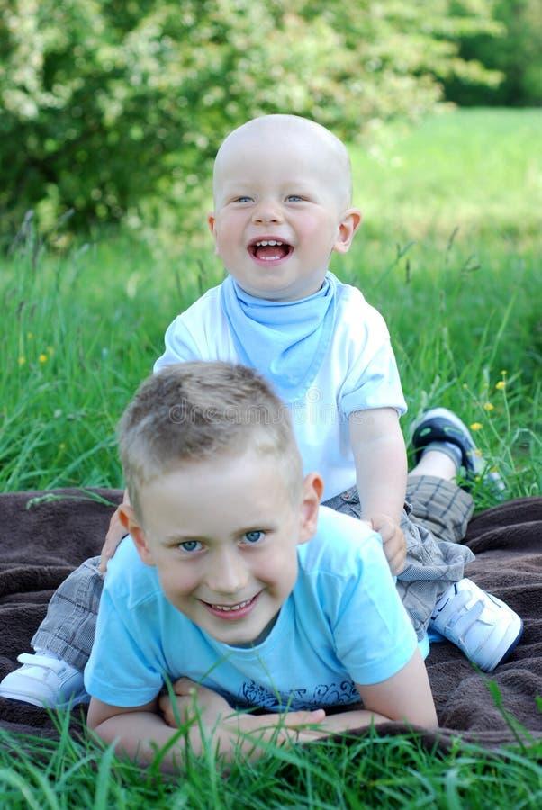 Lyckliga bröder utomhus i sommar arkivbild