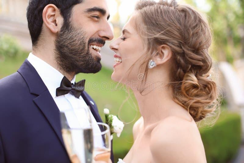 Lyckliga brölloppar med exponeringsglas av champagne utomhus arkivbilder
