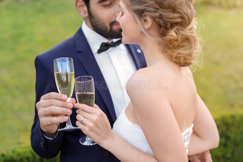 Lyckliga brölloppar med exponeringsglas av champagne utomhus royaltyfri bild