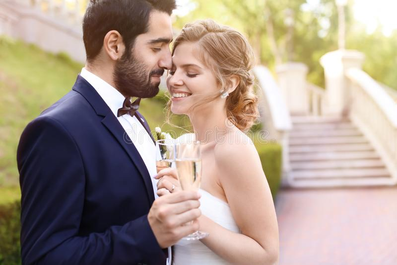 Lyckliga brölloppar med exponeringsglas av champagne utomhus fotografering för bildbyråer