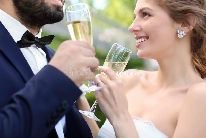 Lyckliga brölloppar med exponeringsglas av champagne utomhus royaltyfria foton