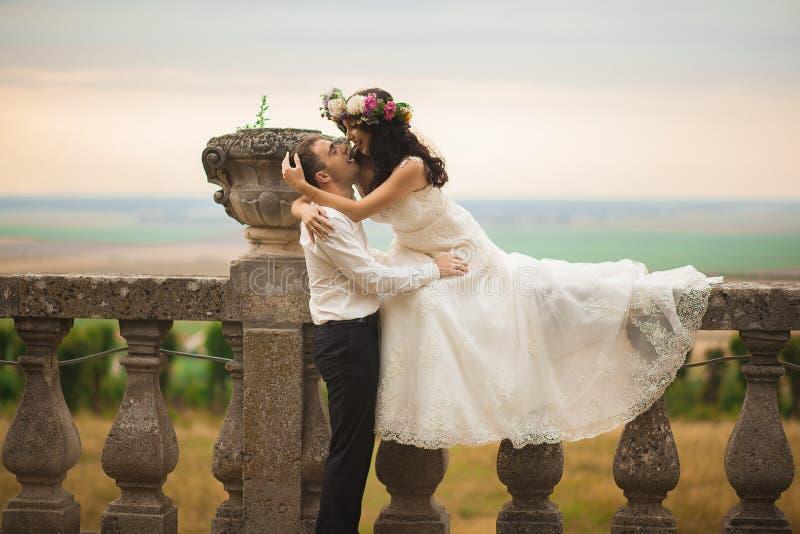 Lyckliga brölloppar som kramar och kysser på gammal slott för bakgrund fotografering för bildbyråer