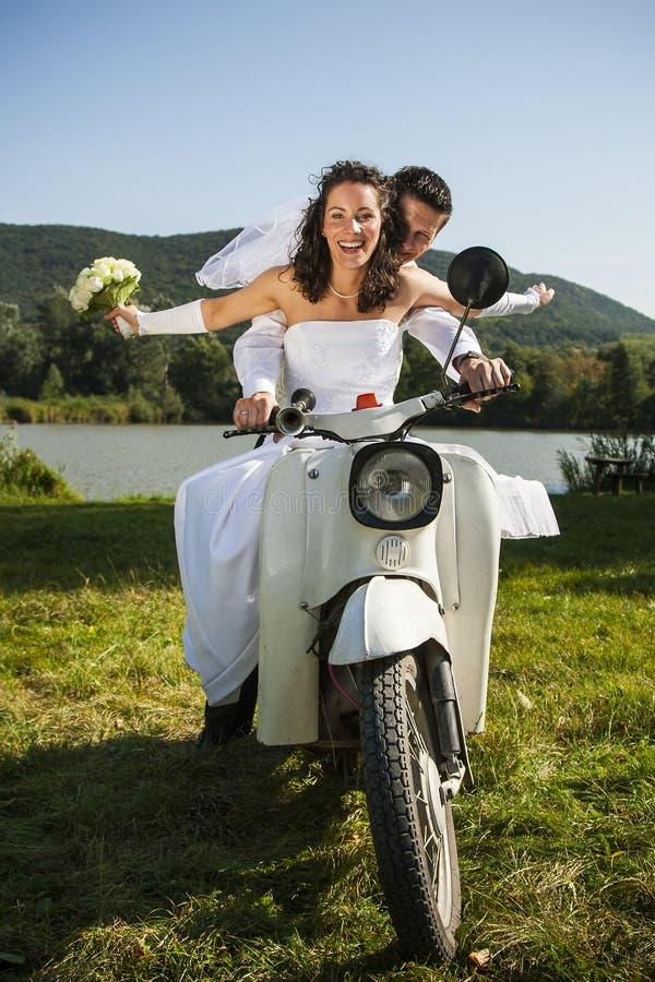 Lyckliga brölloppar tar en ritt i en vit motorcykel. arkivfoto