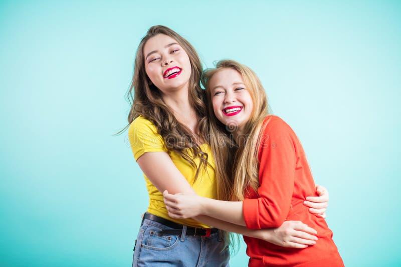 Lyckliga brightful positiva ögonblick av två stilfulla flickor som kramar på blå bakgrund Roligt glat attarctive barn w för Close royaltyfri fotografi