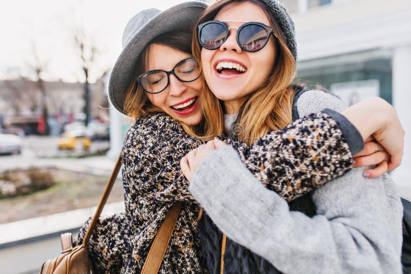 Lyckliga brightful positiva ?gonblick av tv? stilfulla flickor som kramar p? gatan i stad Roligt glat för Closeupstående royaltyfri foto