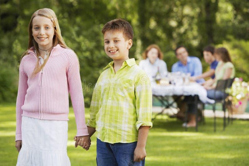 Lyckliga broderAnd Sister Holding händer i trädgård royaltyfri fotografi