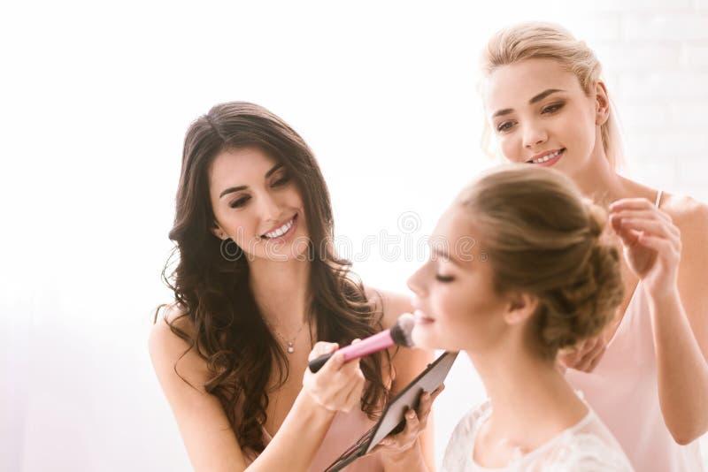 Lyckliga brudtärnor som hjälper bruden att få klar royaltyfri foto