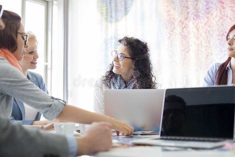 Lyckliga businesspeople som diskuterar under möte i idérikt kontor royaltyfria bilder