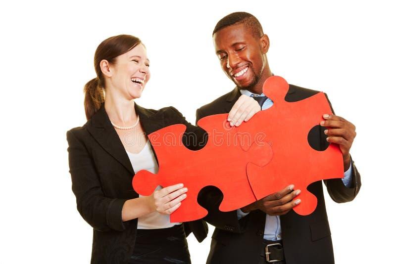 Lyckliga businesspeople som löser pusslet fotografering för bildbyråer