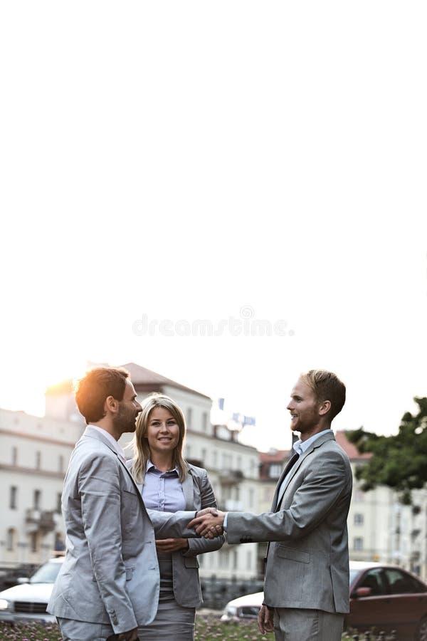 Lyckliga businesspeople som skakar händer i stad mot klar himmel royaltyfri bild