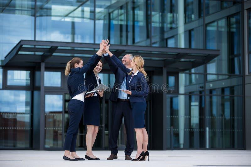 Lyckliga businesspeople som till varandra ger höjdpunkt fem arkivfoto