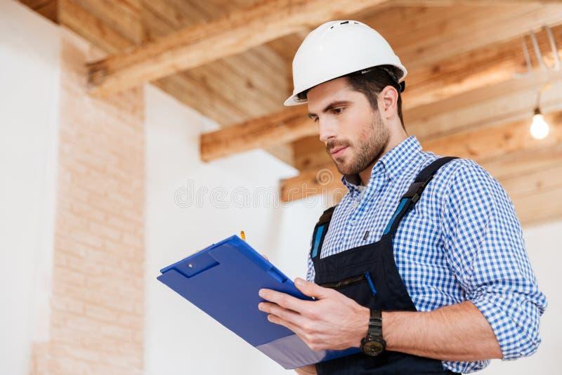 Lyckliga byggmästarehandstilanmärkningar i hardhat med skrivplattan arkivfoton